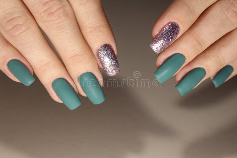 La progettazione del manicure è verde con argento fotografie stock libere da diritti