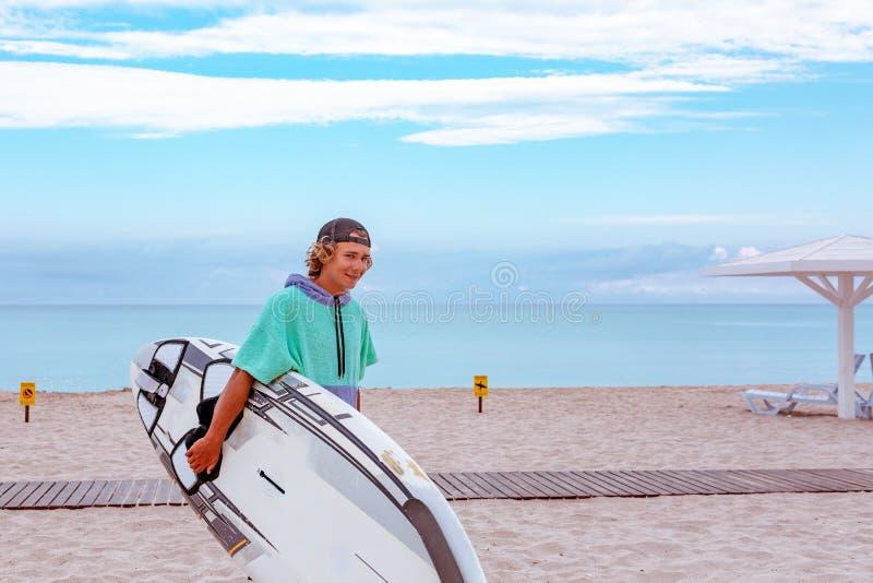 La promenade belle d'homme avec l'attente vide blanche de conseil surfant saluent la tache de ressac au rivage d'océan de mer Vue photo libre de droits