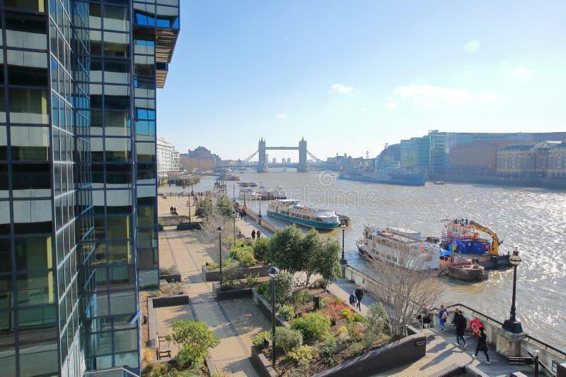 La promenade de rive est le long de la Tamise avec le pont de tour dans le fond et les péniches dedans le premier plan images stock