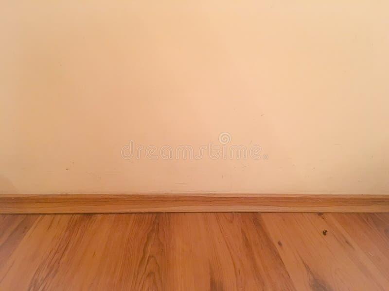 La prospettiva di legno del pavimento della stanza, pastello di lerciume ha dipinto il muro di cemento e il grou laminato di legn fotografia stock