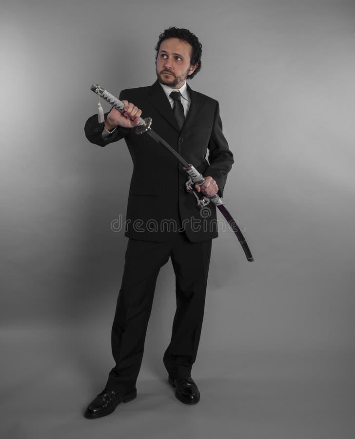 La protección, hombre de negocios agresivo con las espadas japonesas adentro defen imagen de archivo