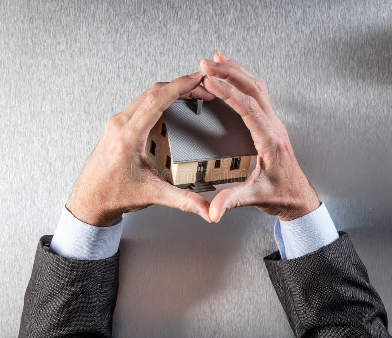 La protección respetuosa del medio ambiente del edificio con el hombre de negocios da el abarcamiento de una casa fotografía de archivo libre de regalías