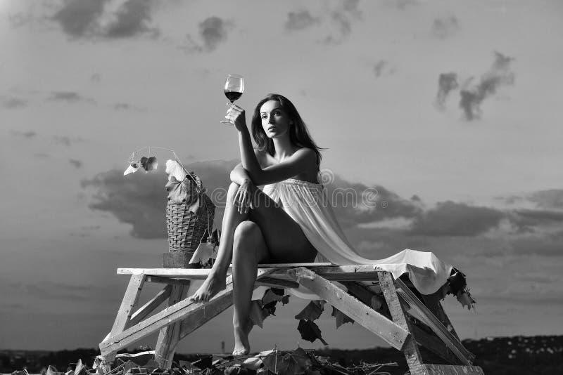 La publicité du vin Jolie femme avec du vin au-dessus du ciel photos stock