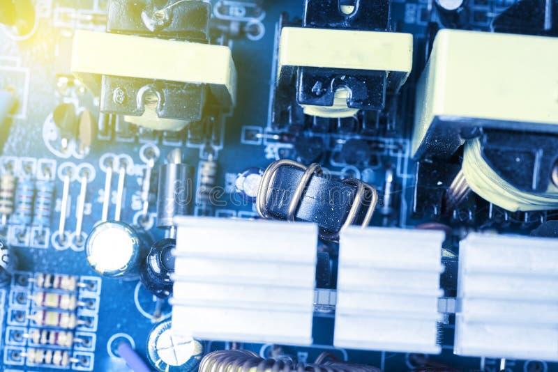 La puce, les condensateurs, résistances sur un ordinateur bleu embarquent Fond industriel photos libres de droits