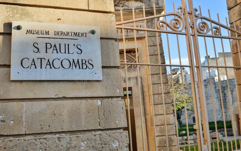 La puerta cerrada de la entrada con la muestra a las catacumbas y al museo de San Pablo en una pared de la piedra arenisca imágenes de archivo libres de regalías