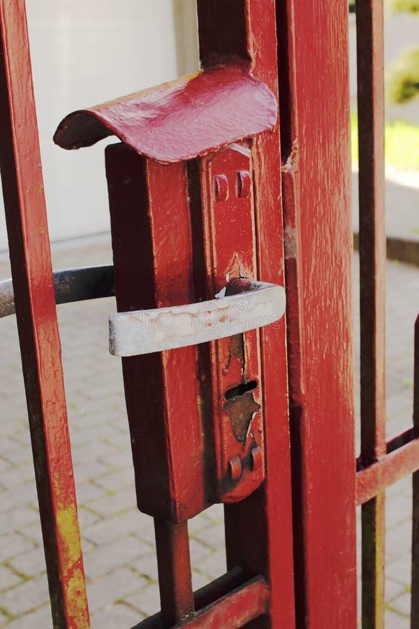 La puerta coloreada roja de la puerta del metal se cerró con el tirador de puerta de acero fotografía de archivo