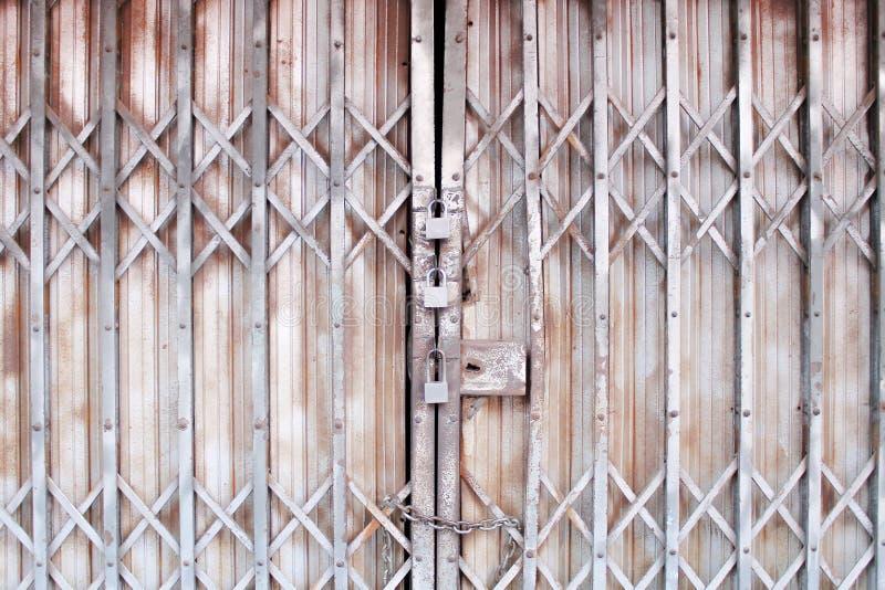 La puerta de acero plegable gris adentro entrelaza los modelos para el fondo y tres bloqueados viejos oxidados fotos de archivo libres de regalías