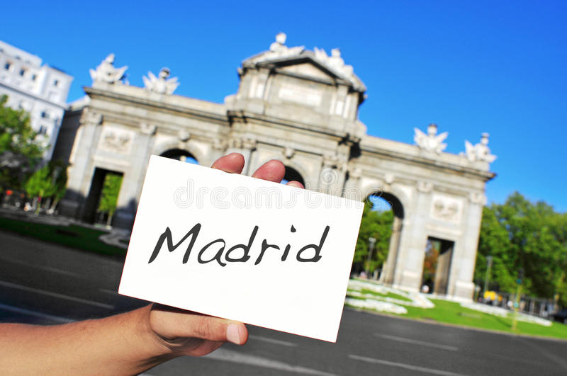 La Puerta de Alcala in Madrid, Spain. A man holding a signboard with the word Madrid written in it in front of La Puerta de Alcala in Madrid, Spain royalty free stock photography