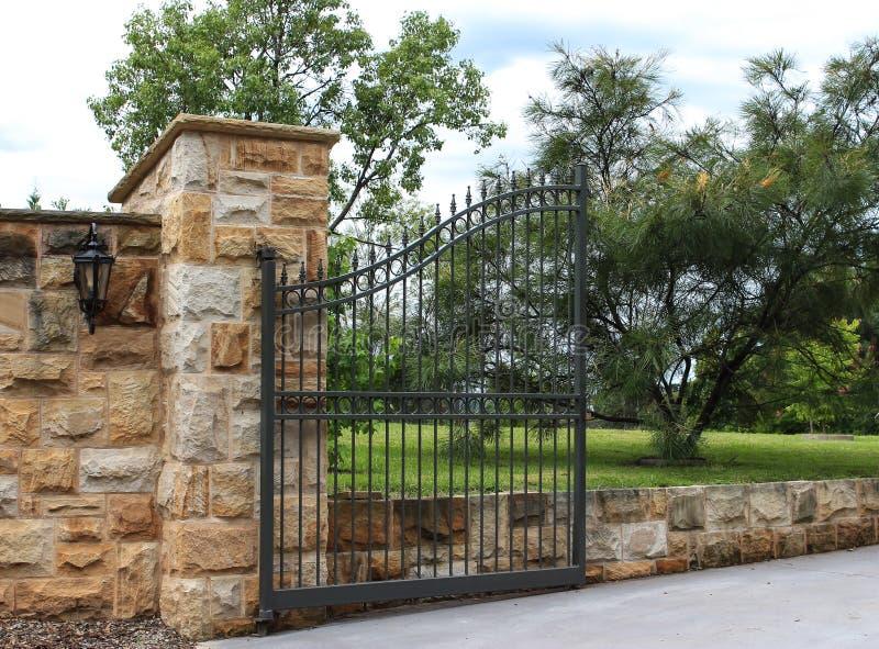La puerta de la entrada del hierro labrado fijó en cerca de la piedra arenisca fotografía de archivo