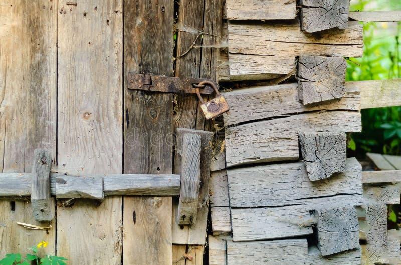 La puerta de madera auténtica y un vintage se cierran en un lazo oxidado, concepto de viejos objetos fotos de archivo libres de regalías