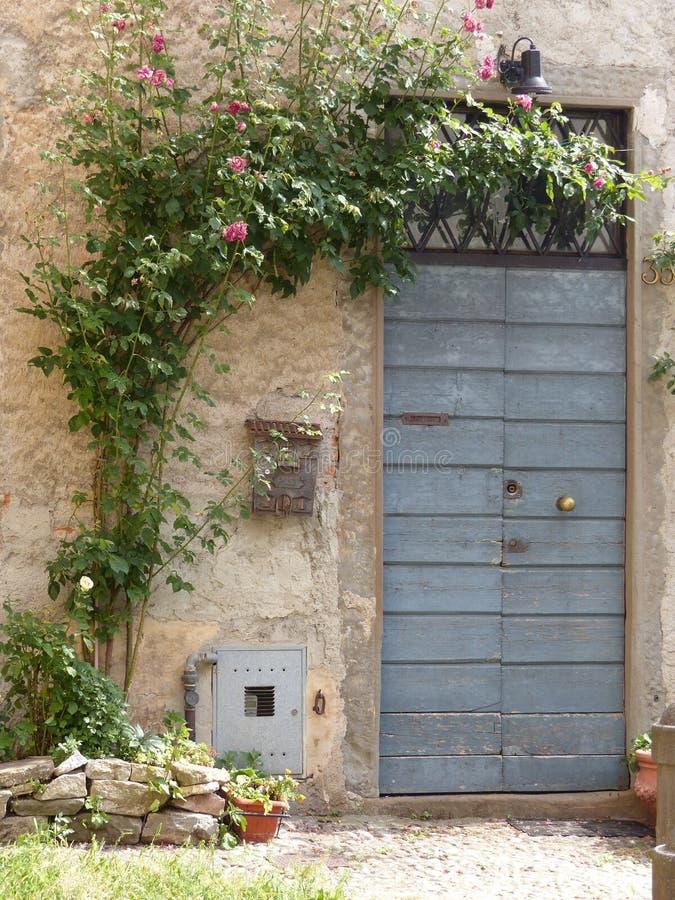 La puerta de madera azul con las rosas planta alrededor B?rgamo Italia imagen de archivo