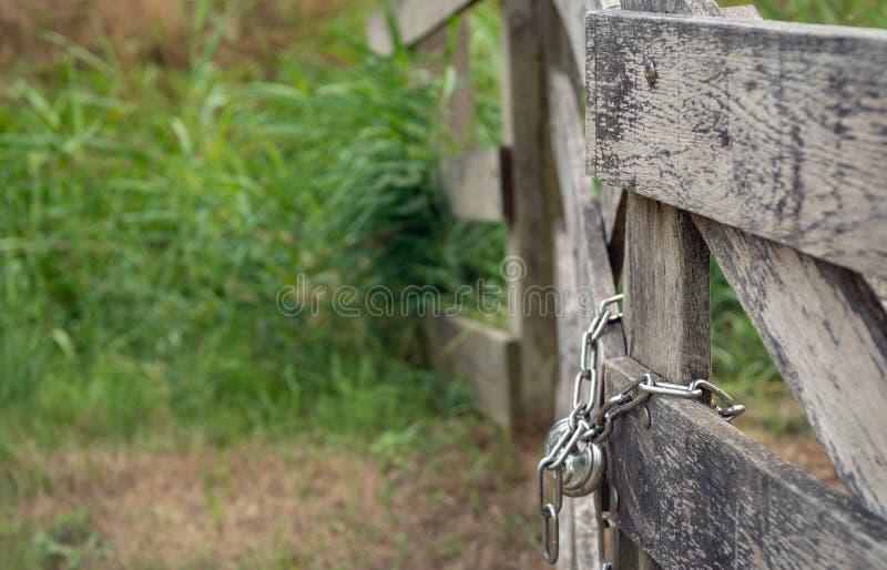 La puerta de madera resistida se cerró con la cadena y el candado brillantes imagen de archivo libre de regalías