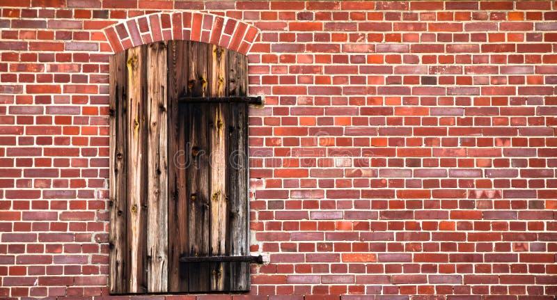 La puerta de madera roja marrón cerrada con el metal aherrumbrado se articula en una pared de ladrillo roja sucia de un granero v fotografía de archivo