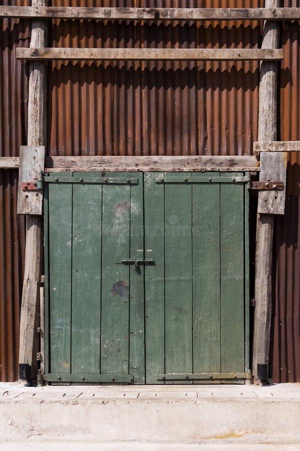 La puerta de madera verde vieja hecha de tabl?n en la pared acanal? la cerca del cinc con el viejo marr?n superficial oxidado par imagen de archivo