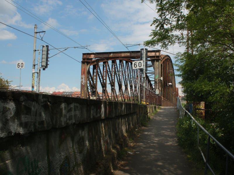 La puerta para el tren a la Praga - cerque el puente con barandilla sobre el río Moldava fotografía de archivo