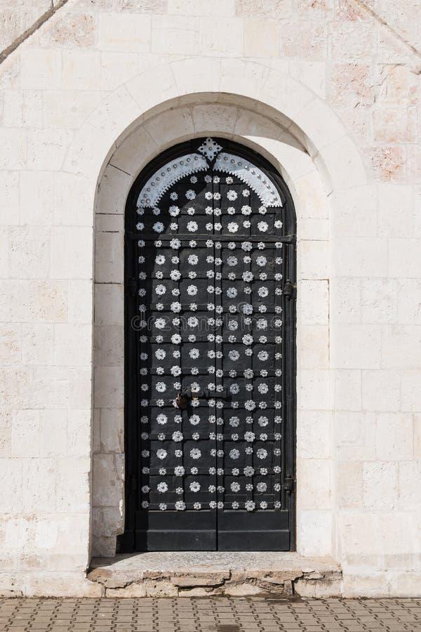 La puerta principal est? en una pared de piedra antigua, el metal viejo que se cierra la puerta del hierro labrado Cerradura cerr imágenes de archivo libres de regalías