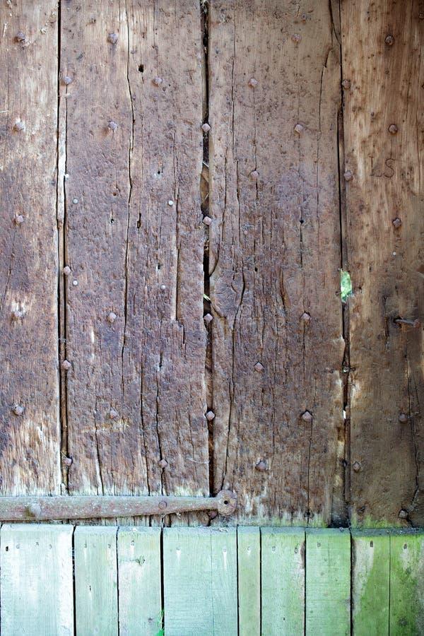 La puerta resistida vieja del roble con verde pintó el fondo de la parte imagenes de archivo