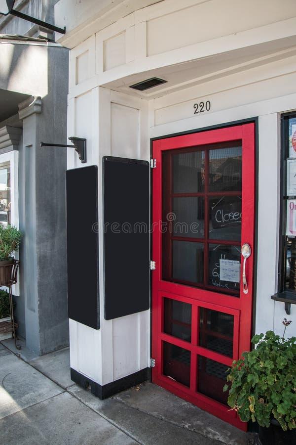 La puerta roja del restaurante con un cerrado firma adentro la ventana Hay dos marca a tableros con tiza en blanco cerca de la pu fotos de archivo
