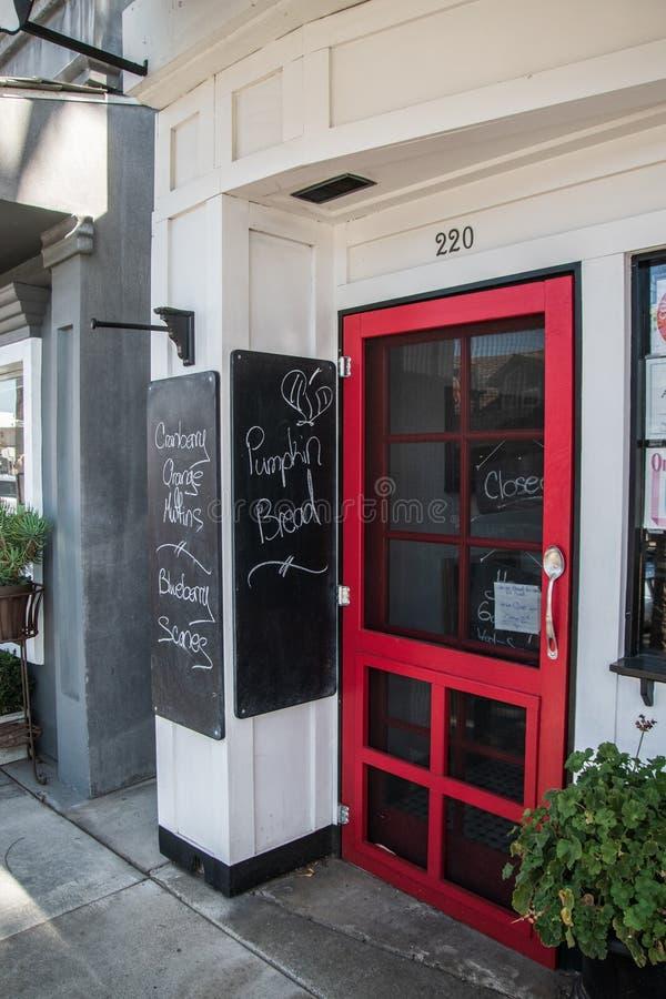 La puerta roja del restaurante con un cerrado firma adentro la ventana Hay dos tableros de tiza que hacen publicidad de reposterí foto de archivo libre de regalías