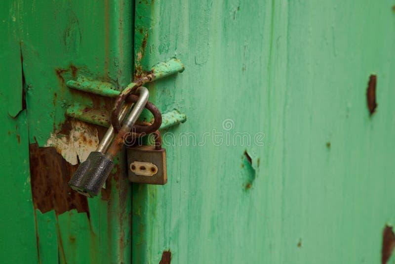 La puerta verde es cerrada en dos candados PROTECCIÓN DOBLE imagen de archivo