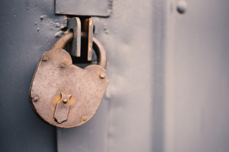 La puerta vieja se cerró con los soportes de una ejecución del candado Sistema de fondos imagen de archivo