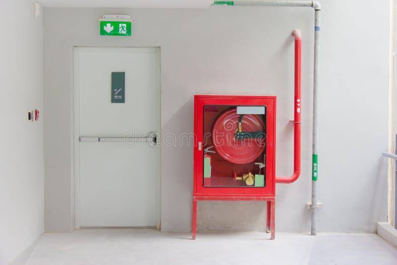 La puerta y el fuego de la salida de socorro extinguen el equipo imagen de archivo libre de regalías