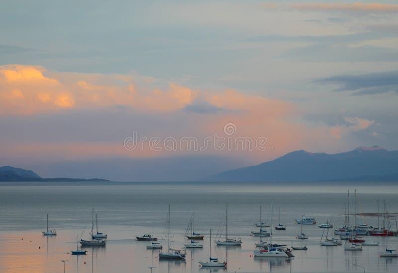 La puesta del sol baja sobre el puerto de Ushuaia y del canal del beagle foto de archivo