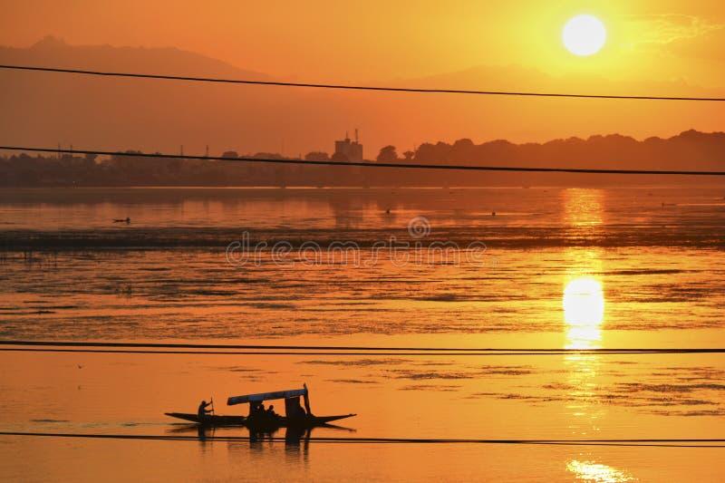 La puesta del sol colorida hermosa sobre Dal Lake con el barco de madera tradicional tomado de Nishat Bagh cultiva un huerto en S fotografía de archivo libre de regalías