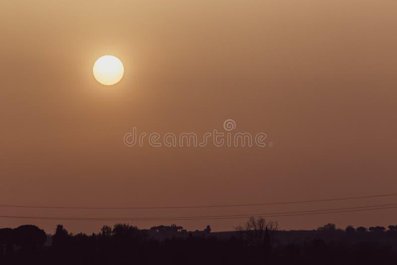 La puesta del sol con la arena suspendió en la atmósfera, coluring el rojo del cielo, sobre siluetas de algunos árboles y líneas  fotografía de archivo