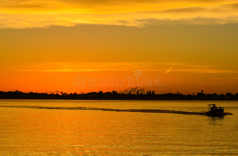 La puesta del sol con la silueta de un barco en el costero inter en Belleair fanfarronea, FloridaSunset con la silueta de un barc fotos de archivo