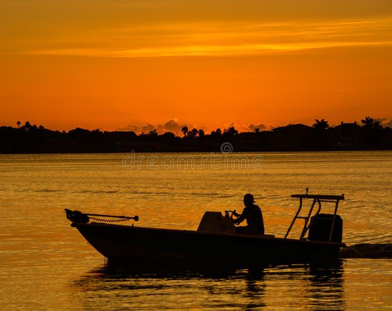 La puesta del sol con la silueta de un barco en el costero inter en Belleair fanfarronea, FloridaSunset con la silueta de un barc imagenes de archivo