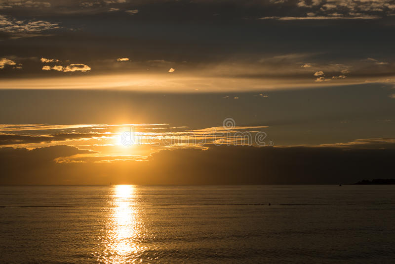 La puesta del sol de oro hermosa en el mar adriático tranquilo, haz pasado del sol hace una trayectoria de oro en superficie wave fotos de archivo