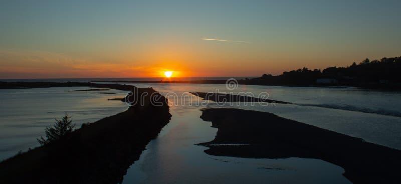 La puesta del sol en la boca del río del granuja de Oregon imagen de archivo