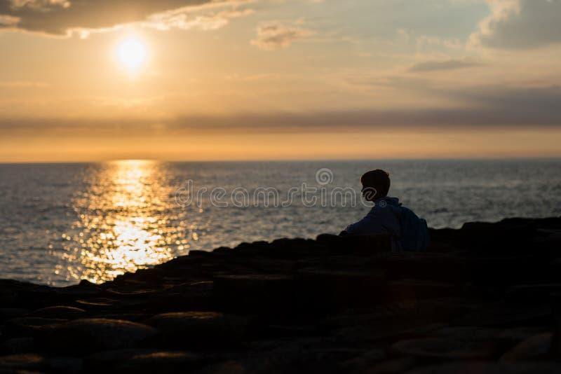 La puesta del sol en el lado de mar, reflejo de luz en la superficie del agua, niño pequeño se sienta en el silhuoette de la play imágenes de archivo libres de regalías