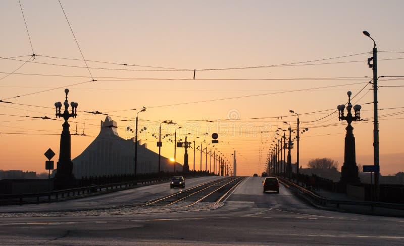 La puesta del sol en el puente de piedra Akmens inclina en Riga fotografía de archivo