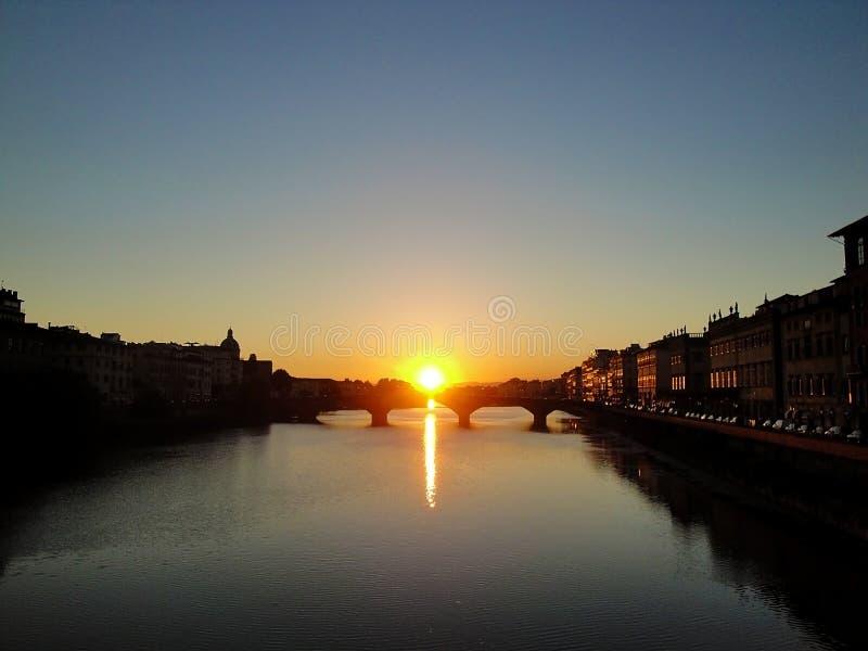 La puesta del sol en el río de Arno en Florencia 0 Italia imágenes de archivo libres de regalías