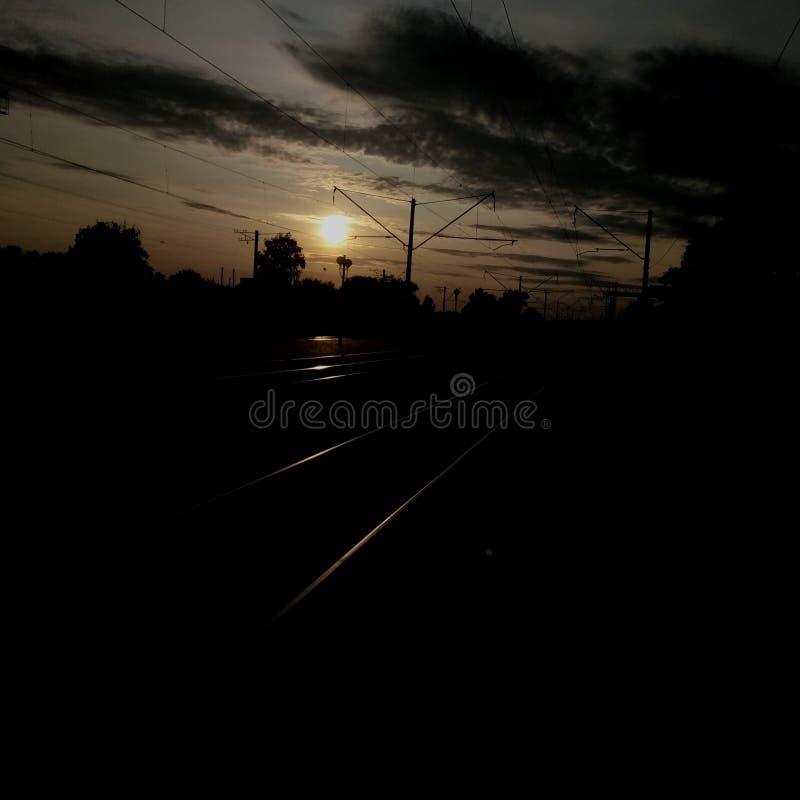 La puesta del sol en la estación de tren foto de archivo
