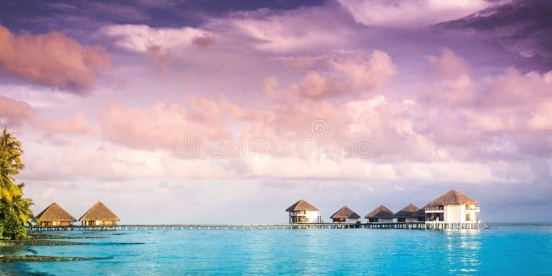 La puesta del sol en la isla de Maldivas, chalets del agua recurre fotografía de archivo libre de regalías