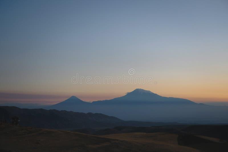La puesta del sol en las montañas, los rayos del sol hace su manera a través de la corona del árbol foto de archivo libre de regalías