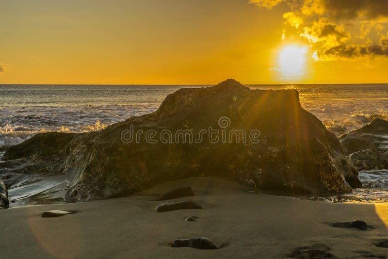 La puesta del sol en la playa de Fuerteventura con lava oscila imágenes de archivo libres de regalías