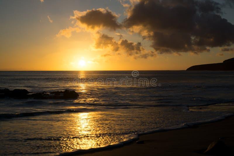 La puesta del sol en la playa de Fuerteventura con lava oscila imagen de archivo