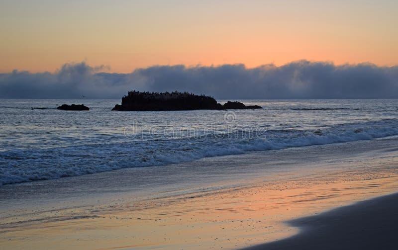 La puesta del sol en roca del pájaro y la línea de la playa debajo de Heisler parquean en el Laguna Beach, California foto de archivo libre de regalías