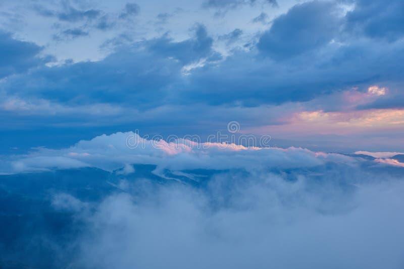 La puesta del sol ilumina las nubes sobre un valle verde de la montaña en la niebla imágenes de archivo libres de regalías