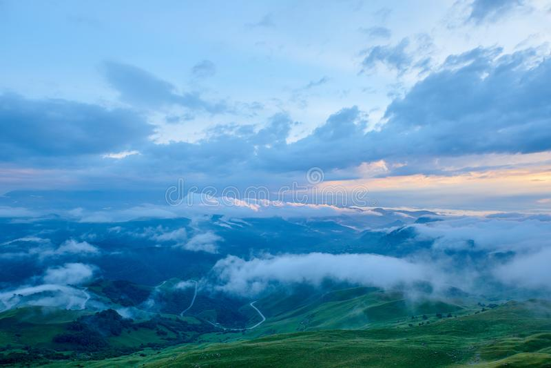 La puesta del sol ilumina las nubes sobre un valle verde de la montaña en la niebla imagen de archivo