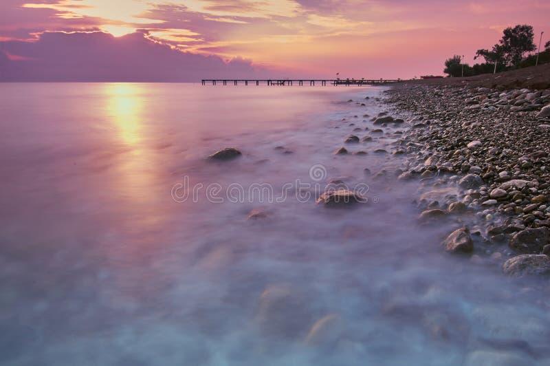 La puesta del sol o el paisaje de la salida del sol, panorama de la naturaleza hermosa, playa con las nubes rojas, anaranjadas y  imagenes de archivo