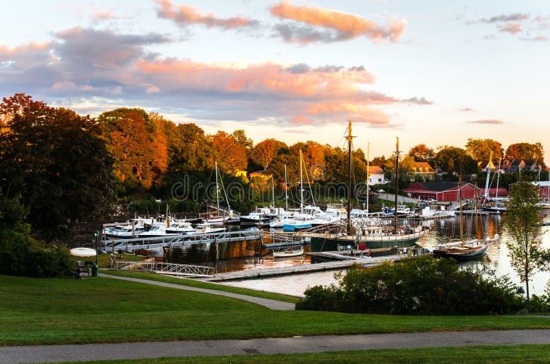 La puesta del sol otoñal sobre un puerto con los barcos amarró los embarcaderos de madera del ot imagen de archivo