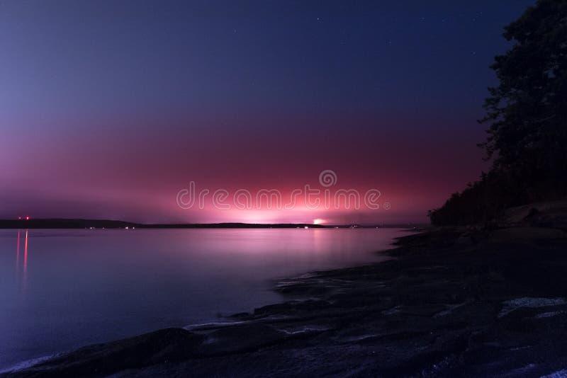 La puesta del sol púrpura de la altura todavía riega la reflexión y las montañas en Canadá fotos de archivo