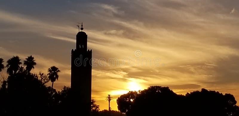 La puesta del sol por la mezquita Marrakesh, Marruecos de Koutoubia es el monumento visitado imagenes de archivo
