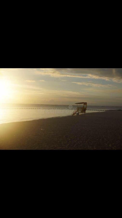 La puesta del sol relaja la bahía triste de la playa imagenes de archivo