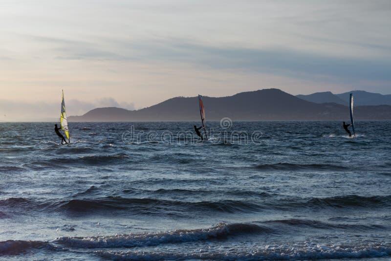 La puesta del sol sobre el mar o el océano y el estilo libre extremo se divierten el windsur fotografía de archivo libre de regalías